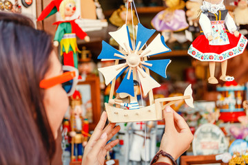 Woman customer looking at wooden toys at the souvenir market