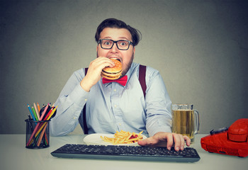 Hungry man eating fast food at work