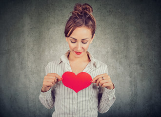 Content woman holding red heart on chest