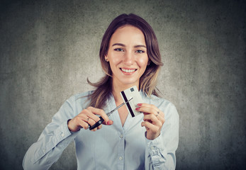 Happy woman cutting credit card