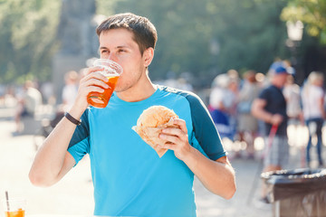 Man outdoors Eating Burgers and drinking beer at street food festival
