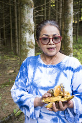 Thai old woman people hunter-gatherer and picking mushroom in forest