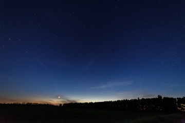 Bright star-planet Venus over the field and forest against the starry sky at dusk.