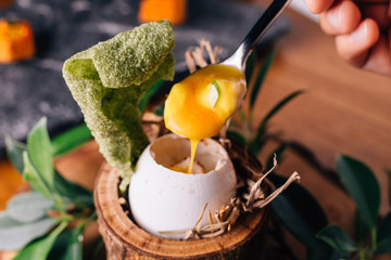 Creative Fine Dinning: Soft-boiled eggs scoop cheese and yolk with shell decorated with small branches, leaves and straw.