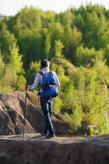 Photo from back of young tourist with walking sticks on hill on background of vegetation