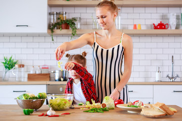 Image of woman with her daughter cutting vegetables in kitchen