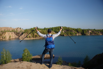 Photo from back of young tourist with backpack with arms raised with walking sticks on background of mountain landscape