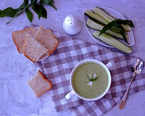 Summer cold yoghurt soup with fresh cucumber, green peas and mint on a gray concrete background