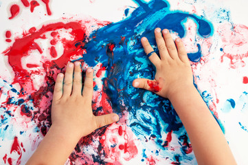 Painted hands smudging colors on messy paper