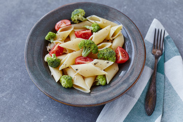 Pasta penne with broccoli on grey stone table. Healthy vegetarian food.