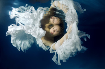 Young beautiful woman in the image of an angel underwater