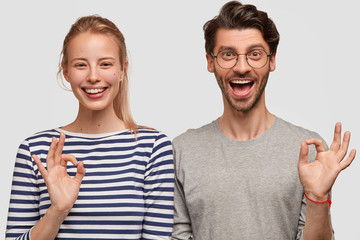 Horizontal shot of glad cheerful woman and man have joy together, make okay gesture, show satisfaction with good recreation, share impressions with friends, recommend visit this place for rest