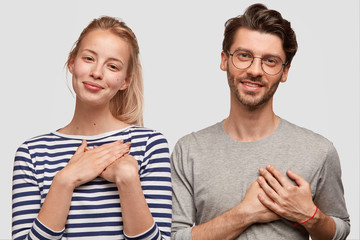 Friendly brother and sister with gentle smiles, have positive expression, keep hands on heart, expresse good attitude to other people, pose together against white background. People and feeling