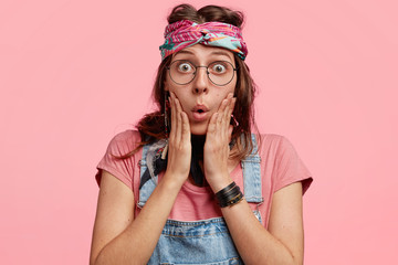 Portrait of amazed and wondered female stares at camera with surprised expression, sees some unexpected things in front, wears stylish headband, keeps hands on cheeks, isolated on pink blank wall