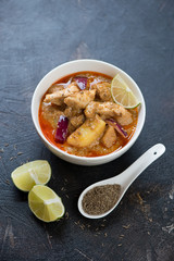 Massaman curry with chicken over dark brown stone background, vertical shot