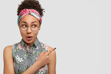 Horizontal shot of amazed mixed race female model in eyewear, indicates aside with fore finger, shows space for your promotion, isolated over white background. African American woman wonders