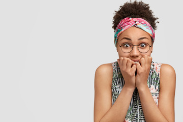 Portrait of scared nervous dark skinned young female bites finger nails, looks worried and anxious, has deadline for making work and duties, wears stylish headband, isolated on white background