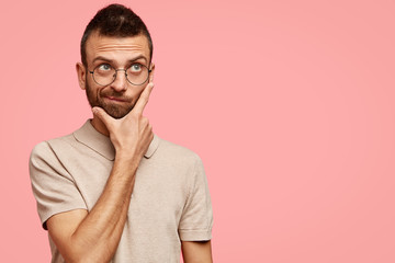 Portrait of thoughtful male with pensive expression, holds chin, focused somewhere, tries to find decision in mind, stands agaisnt pink background with copy space for promotional text. Hipster indoor