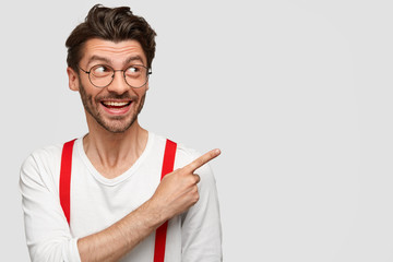 Use this copy space. Cheerful fashionable man with stubble, indicates at upper right corner, demonstrates place for your promotional text, wears glasses, has happy look. People, advertisement concept