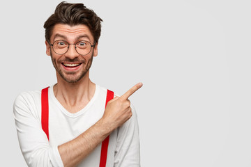 Happy excited male model shows blank space against white background, has dark stubble, trendy haircut, rejoices selling new items in shop, has great mood, expresses optimism and positiveness
