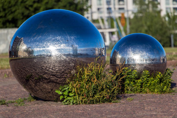 The sun with street is reflected in a two shiny steel ball, Helsinki, Finland
