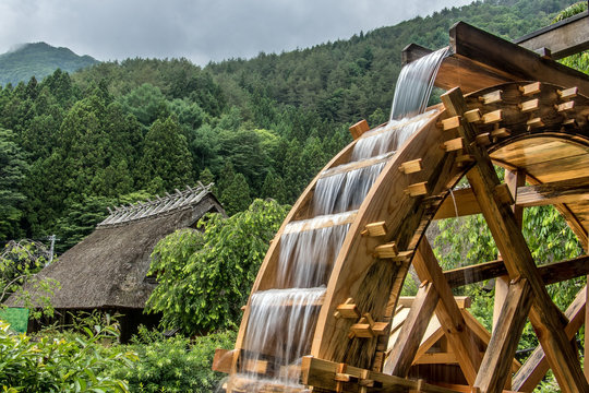 The mill wheel rotates under a stream of water, background of  village with traditional thatched roofed houses