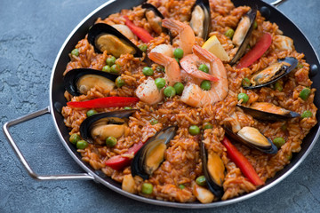 Serving pan with seafood paella over blue stone background, studio shot, closeup