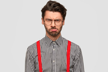 Young fashionable male has stubble, gloomy expression, being dissatisfied with results of work, dressed in stylish outfit, wears round glasses, frowns face in displeasure. Negative facial expressions