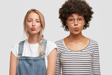 Studio shot of two beautiful mixed race young women make grimace, round lips, shoulder to shoulder, isolated over white background. African American female has crisp dark hair meets with sister