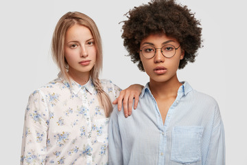 People, interracial friendship and relationship concept. Adorable light haired European woman spends free time with African American female best friend, dressed in fashionable shirts, isolated