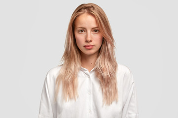Headshot of self assured Caucasian female with healthy pure skin, wears loose white shirt, looks directly into camera, has serious expression, contemplates about future plans. Beauty and lifestyle