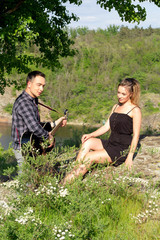 Young attractive man playing guitar for his beautiful girlfriend. Love concept.
