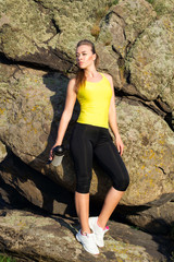 Young beautiful woman relaxing with water in hands after doing sport exercises outdoors
