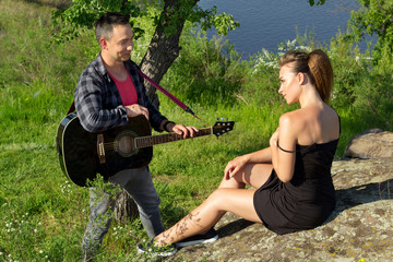 Young attractive man playing guitar for his beautiful girlfriend in park. Love concept.