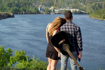 Young couple in love holding hands together standing and looking on river