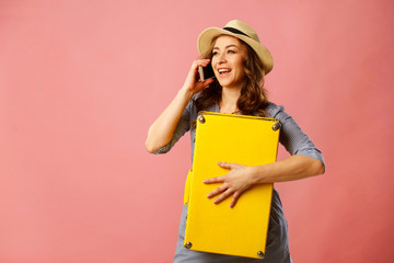 Young happy beautiful woman in hat holding yellow suitcase and talking by mobile over pink background