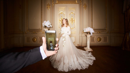 Photographing a bride by the smartphone in luxury interior in the Baroque style.
