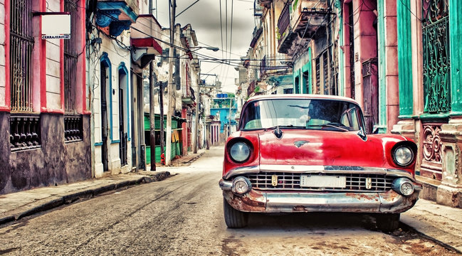 Old red Chevrolet car parked in a street of havana