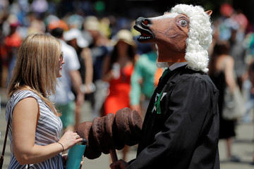 A racing fan wears a horse mask and a judge costume before the 150th running of the Belmont Stakes, the third leg of the Triple Crown of Thoroughbred Racing, at Belmont Park in Elmont, New York