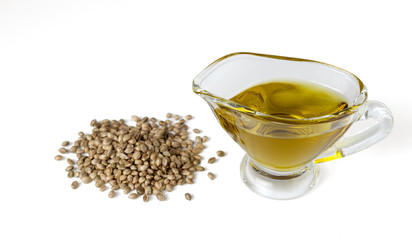 Hemp oil in a glass gravy boat with a bunch of marijuana seeds. Isolated on white background.