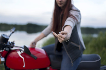 A girl on a motorcycle shows the middle finger