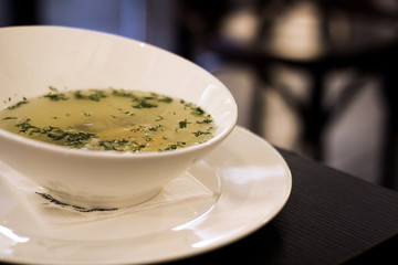 Chicken broth with herbs on a wooden table