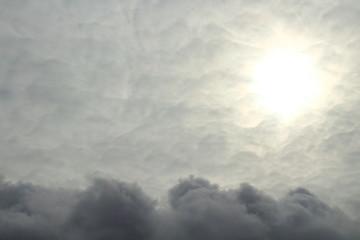 Dark cumulus clouds and pale sun. Overcast. Storm clouds. Background. Landscape. Texture. Spring, April, 2018.