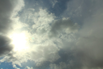 Blue sky and gray clouds. The sun shines through thunderclouds. Background. Landscape.