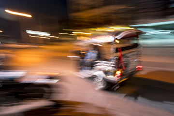 Tuk tuk racing past at night in the streets of Chiang Mai in northern Thailand
