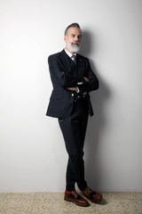 Portrait of confident bearded middle aged gentleman wearing trendy suit standing over empty white background. Studio shot. Vertical