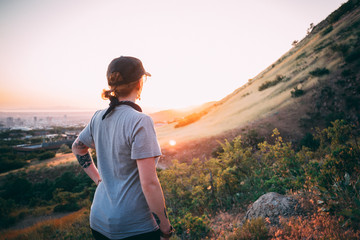 Girl hiking and looking at sunset