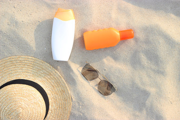 sunscreen, towel, glasses on a sand background view from above. flatlay