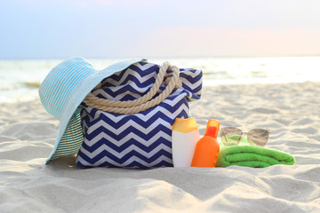 hat, beach bag, sunscreen, glasses and towel on the beach on the background of the sea