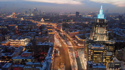 """Aerial shooting of Moscow Garden Ring in the evening. City lights in the dusk. Business center """"Armory"""" tower at sunset."""